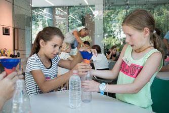 Zwei Forscherinnen dichten eine Flasche mit Knete ab (Foto: B. Budig)