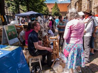Andreas Ostmeyer am Spinnrad erklärt den Besuchern, wie das Spinnen funktioniert. - Foto: Kathy Büscher
