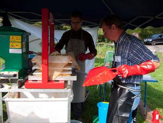 Die ehrenamtlichen des NABU verarbeiten an der mobilen Presse Äpfel zu Saft. - Foto: Kathy Büscher