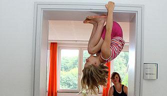 Ein Mädchen hält sich über Kopf hängend im Türrahmen