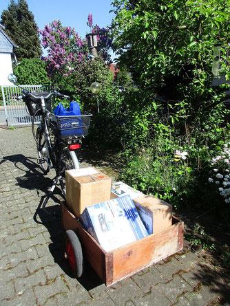 Fahrrad mit Anhänger mit einigen Paketen voller Handys darauf
