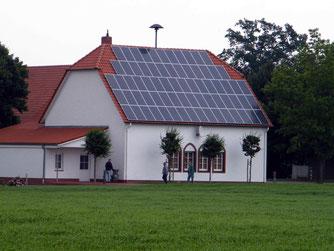 und von der Rückseite mit dem 2004 erbauten Dorfgemeinschaftsraum und der 2010 aufgestellten PV-Anlage.