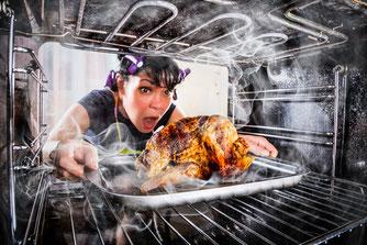 Frau mit Lockenwicklern in den Haaren zieht entsetzt ein verbranntes Brathähnchen aus dem Ofen.