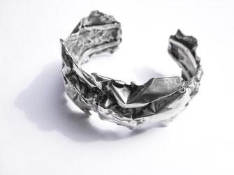 Un gros bracelet rigide et large au design froissé est posé sur fond blanc.