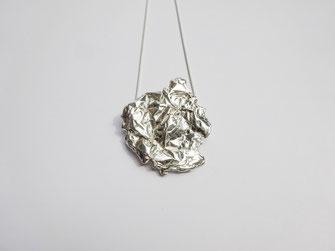 Un très gros pendentif au design froissé est placé sur une chaine fine en argent.