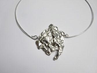 Un collier avec un gros motif en argent froissé tient sur un fil en argent.