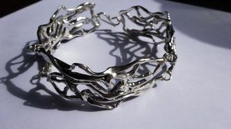 un bracelet ajouré comme de la dentelle est posé sur une feuille blanche.
