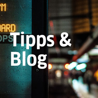 Ausschnitt auf eine digitale Anzeigetafel vor einem unscharfen Bahnsteigausschnitt als Titelbild für die Rubrik Tipps und Blog