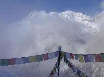 Banderas de oración tibetanas y montañas con nieve