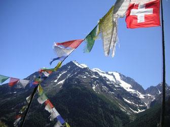 Tibetische Gebetsfahnen und Schweizer Fahne
