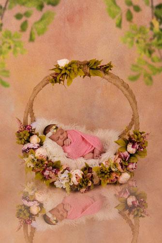 newborn in mandje met bloemen