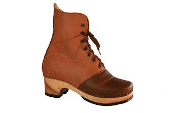 sabots suédois relooké en bottines pour femme sur semelle de bois et talon haut. C'est une véritable chaussure de ville, avec une tige en cuir de couleur camel et l'empeigne en marron foncé pour le contraste. ce modèle est réalisé sur mesure