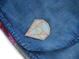!B: ein heller Jeansflicken in Diamantform als Flicken auf einen Rock gebügelt