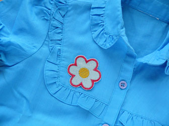 Bild: hellblaues Blumen Bügelbild als Accessoire auf Bluse gebügelt