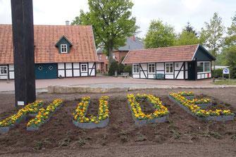 Vor dem Dorfhaus in Hüde formen bunte Blumen in Stahlprofilen den Dorfnamen.