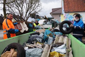 Blick in einen Anhänger mit Müllsäcken, Autoreifen und weiterem Müll.  Am Rand stehen drei Menschen, die weiteren Unrat abladen wollen.