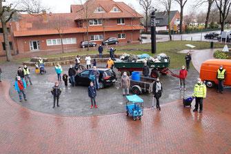 Eine Gruppe Menschen steht auf dem Hüder Dorfplatz unter Einhaltung der Abstandsregel - in der Mitte Anhänger mit Müll und Unrat.