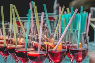 Gruppe Gäser mit rotem Getränk und Strohhalm Sektempfang zum Event