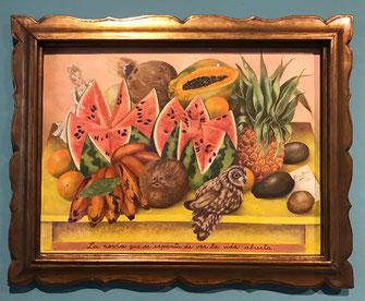 Een watermeloen, kokosnoten, papaya, sinaasappels, avocado's en bananen als een stilleven gerangschikt, met daarop een bruid, die naar dat alles kijkt.