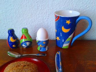 Frühstückstisch gedeckt mit bunter Keramik, wie Eierbecher,Pfefferstreuer, Salzstreuer großer bunter Kaffebecher, nach Hundertwasserart