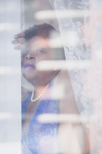 Photo boudoir femme noire taille plus en nuisette bleue à la fenêtre d'un condo de Montréal par Marie Deschene photographe