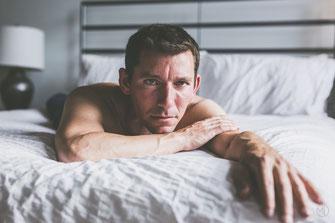 Photo boudoir homme blanc brun torse nu et jean bleu sur lit à Montréal par Marie Deschene photographe
