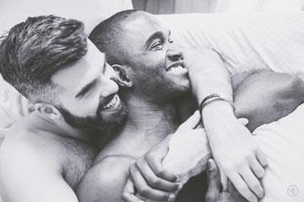 Photo boudoir bw couple mixte gay hommes blanc et noir homosexuel LGBTQ torse nu dans lit à Montréal par Marie Deschene photographe