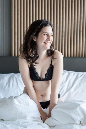 Photo boudoir femme blanche sans maquillage brune  en sous-vêtements noirs sur le lit chambre d'hôtel à Montréal par Marie Deschene photographe