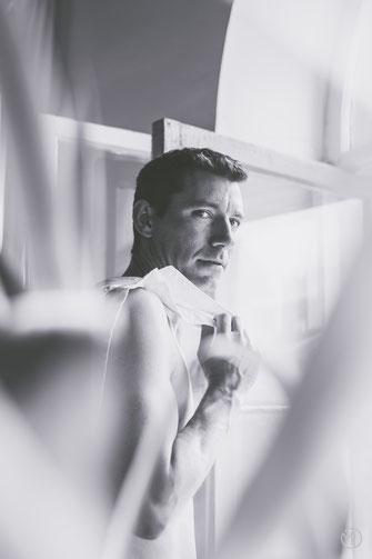 Photo bw noir et blanc boudoir homme blanc brun cheveux courts torse nu et chemise blanche salon bord de fenêtre à Montréal par Marie Deschene photographe