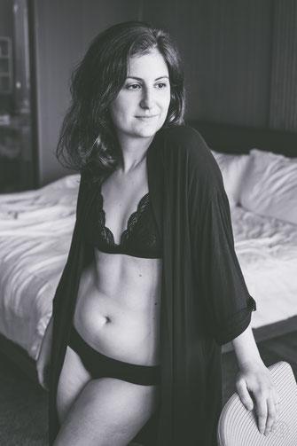Photo noir et blanc boudoir femme blanche pulpeuse tatouée en sous-vêtements sur son lit Rive-Sud de Montréal par Marie Deschene photographe