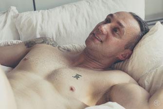 Photo boudoir homme blanc brun torse nu et sous-vêtements tatoué sur lit à Montréal par Marie Deschene photographe
