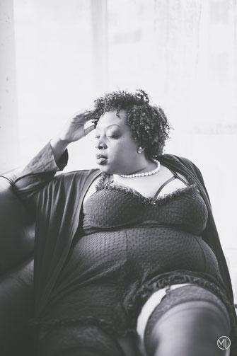 Photo noir et blanc boudoir femme noire taille plus en nuisette noire sur canapé dans un condo de Montréal par Marie Deschene photographe