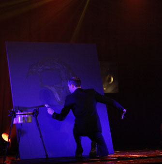 Erik black painting on stage for a live show