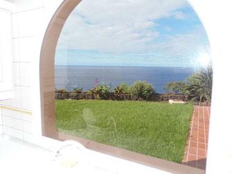 Blick aus dem Küchenfenster der Urlaubswohnung über den grünen Rasen bis zum Meer auf der Nordseite der Insel Teneriffa.
