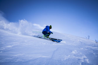 Man in blue jacket skiing