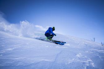 Man in blue jacket skiing