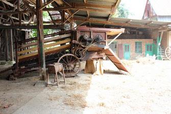 Vieille moissonneuse dans la cour de la ferme