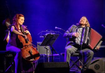 Rothaarige Cellistin im lila Kleid mit blondem Akkordeon-Spieler mit leidenschaftlicher Musik #cellocrossing #duo #minimalmusic