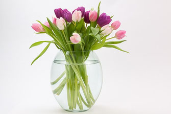 ピンクを基調とした色合いのチューリップの花束がガラスの花びんに活けられている。