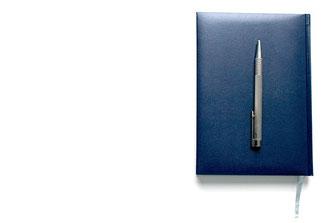 背表紙が青色の手帳と銀色のボールペン