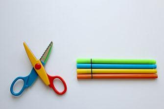 赤・青・黄・緑のカラフルな色合いのはさみと同色のサインペン。