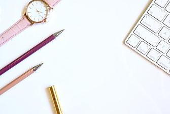 パソコンのキーボードとピンク色の革の腕時計、ピンク色のボールペンが2本、デスクの上に並んでいる。