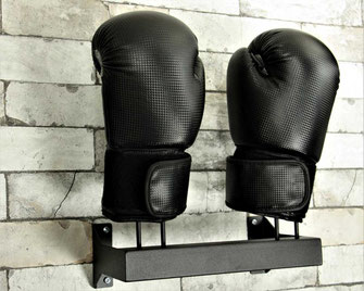 black boxing glove rack with gloves bolted to a brick wal