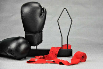 black boxing glove rack with red handwraps on a grey background