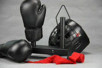 black boxing glove dryer with boxing gloves, helmet and red handwraps on a grey background