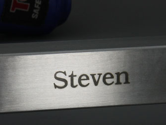 Close up of the name Steven engraved to a stainless boxing glove rack