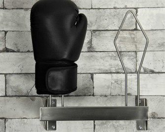 stainless boxing glove rack with a single glove bolted to a brick wall