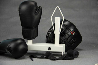 white boxing glove dryer with boxinggloves, helmet and black handwraps on a grey background