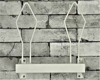 white boxing glove rack  bolted to a brick wal