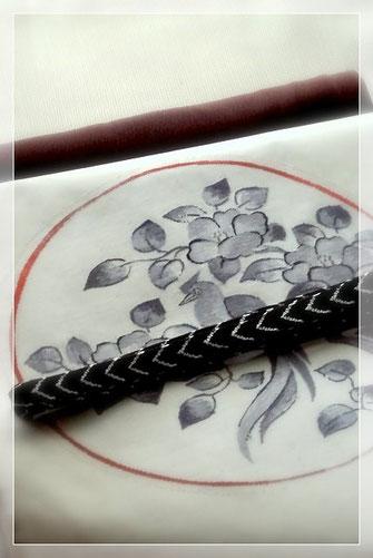薄いベージュの八丈織は菊池洋守作。白地に墨色で椿尾長鳥を織りだしたすくい織の袋帯を合わせました。